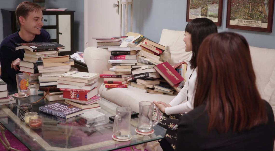 Marie kondo in house with client surrounded by books