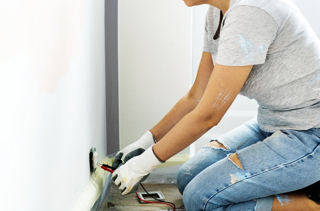 Women installing outlet into the wall