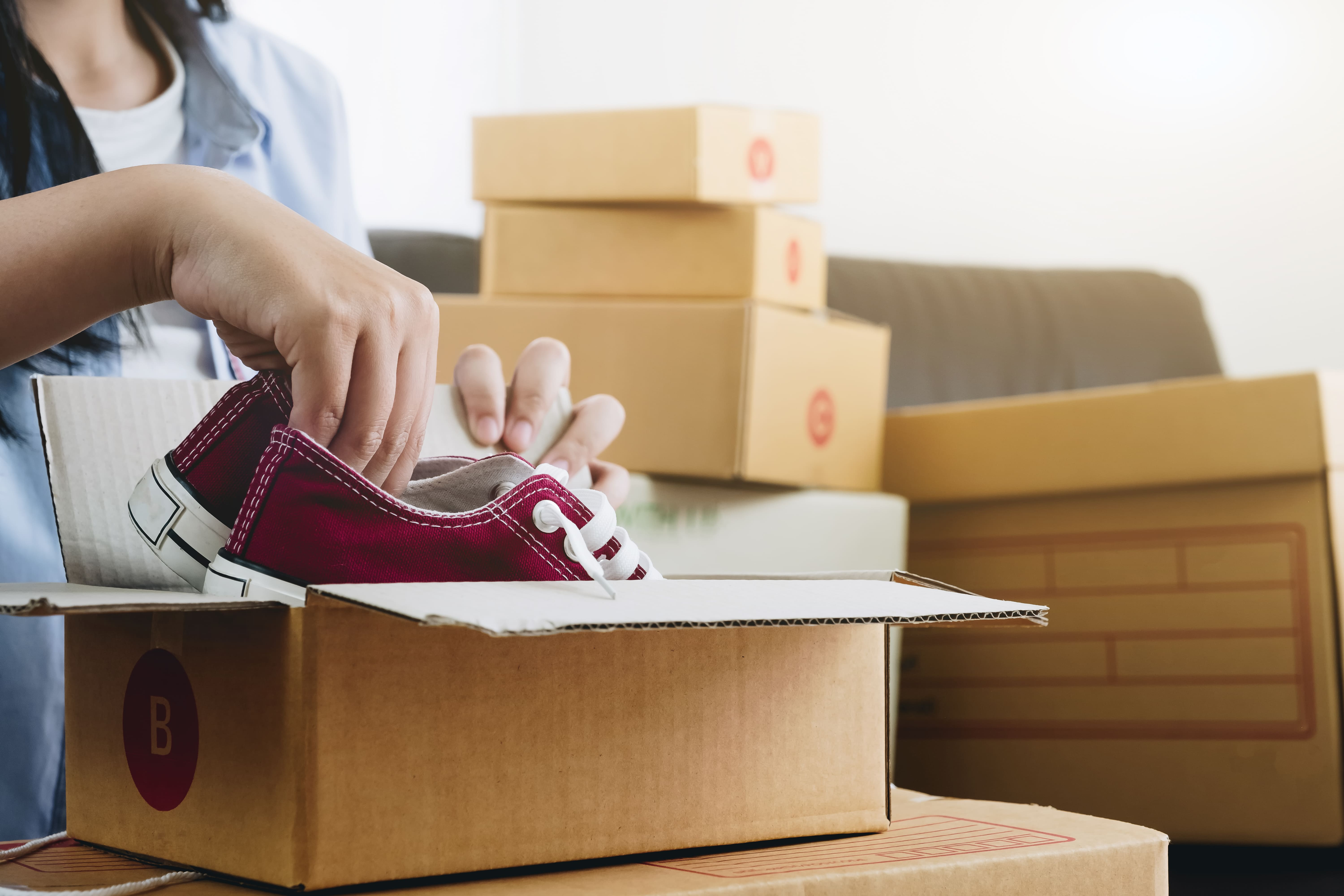woman packing shoes for moving