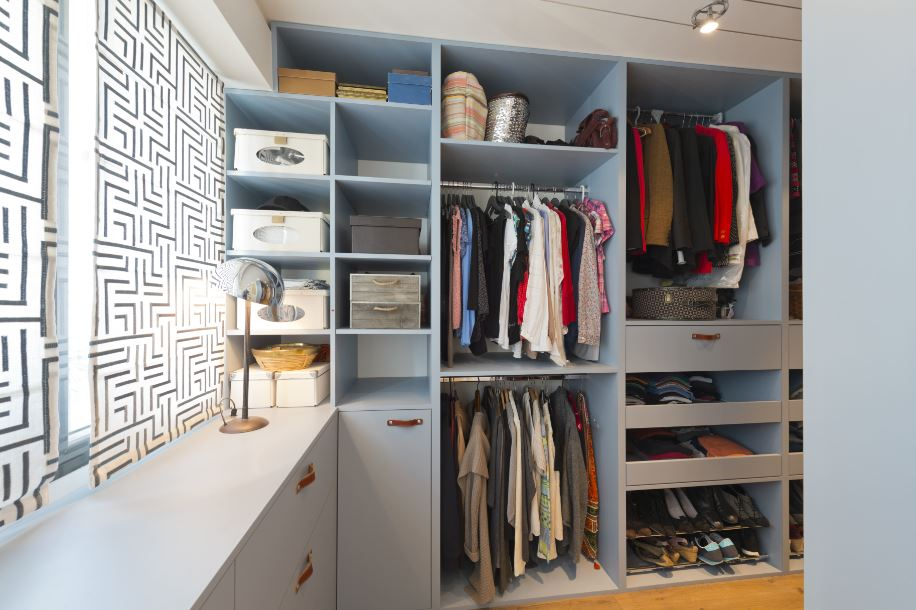 an organized closet with baskets and shelves
