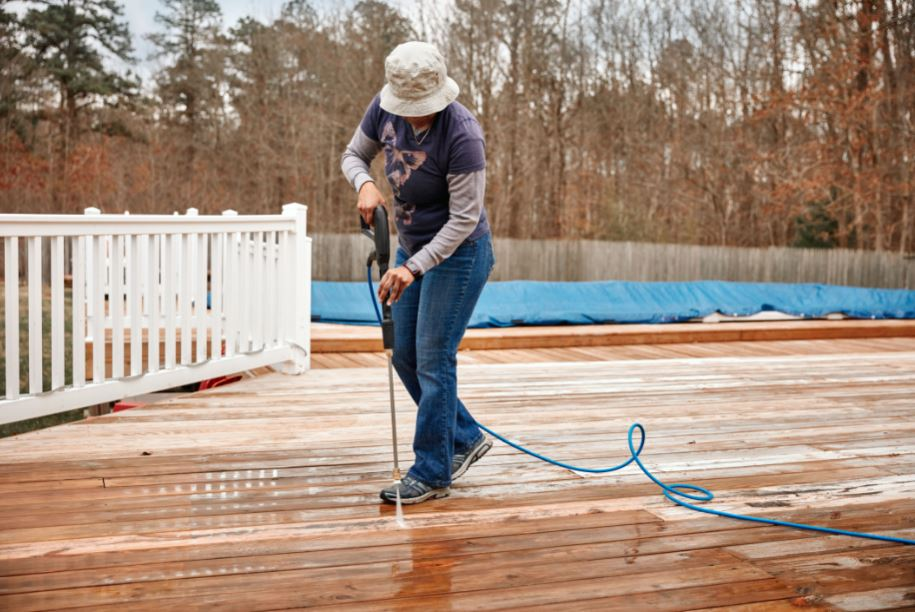 homeowner completing the step by step process of how to pressure wash a deck