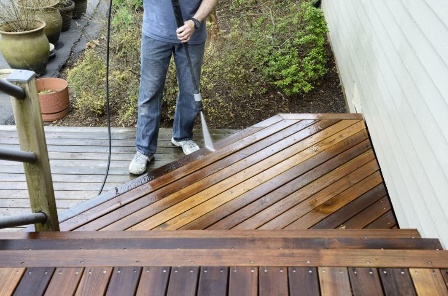 homeowner pressure washing the edge of their deck