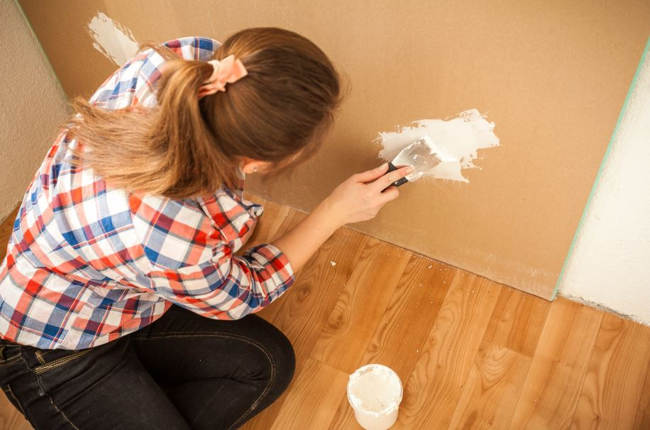 homeowner repairing minor wall damage as part of her moving checklist
