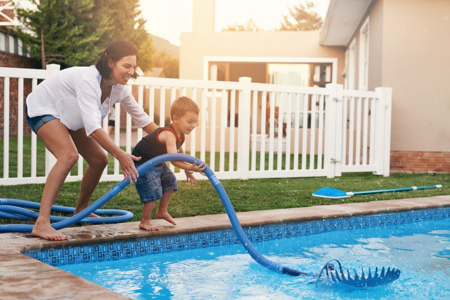 woman and her child cleaning the pool as a summer pool maintenance chore