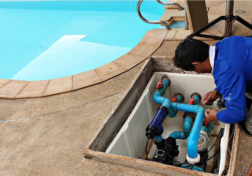 man removing water from a swimming pool's internal components in preparation for winterization and pool maintenance