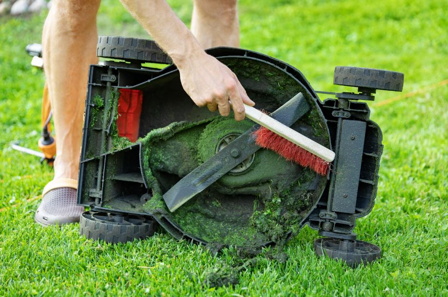 man brushing grass off a lawn mower to clean and winterize the lawn mower