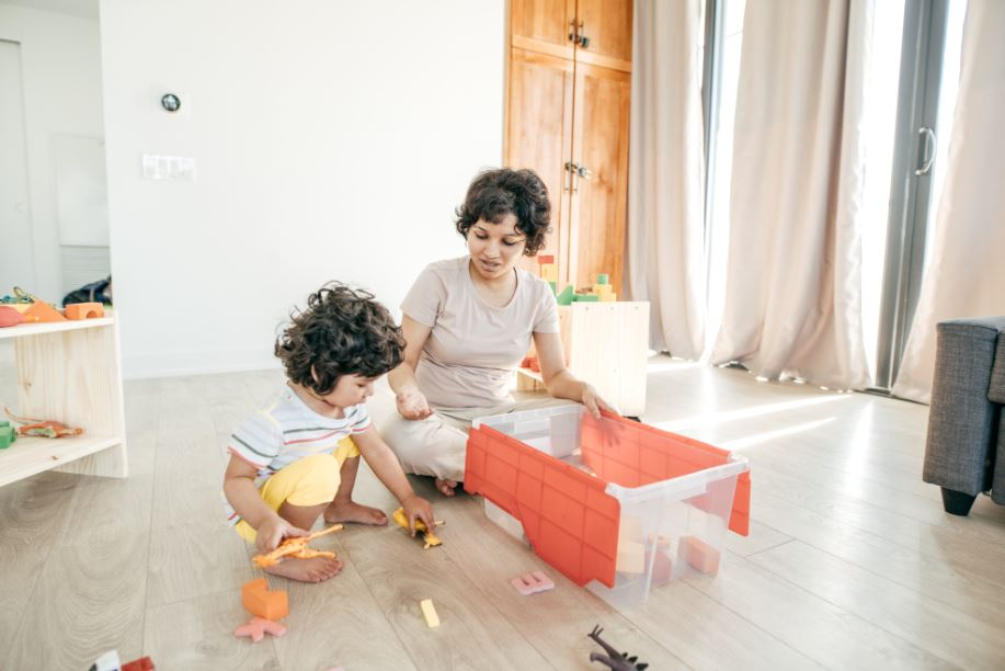 woman organizing toys in the living with her toddler
