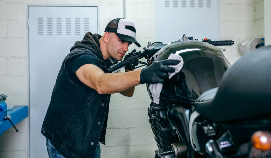 man cleaning his motorcycle in preparation for motorcycle storage