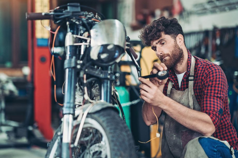 man maintaining his motorcycle before putting it in long-term motorcycle storage