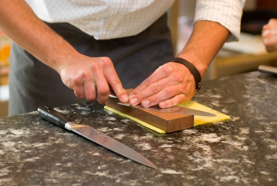 man using a whetstone for knife sharpening