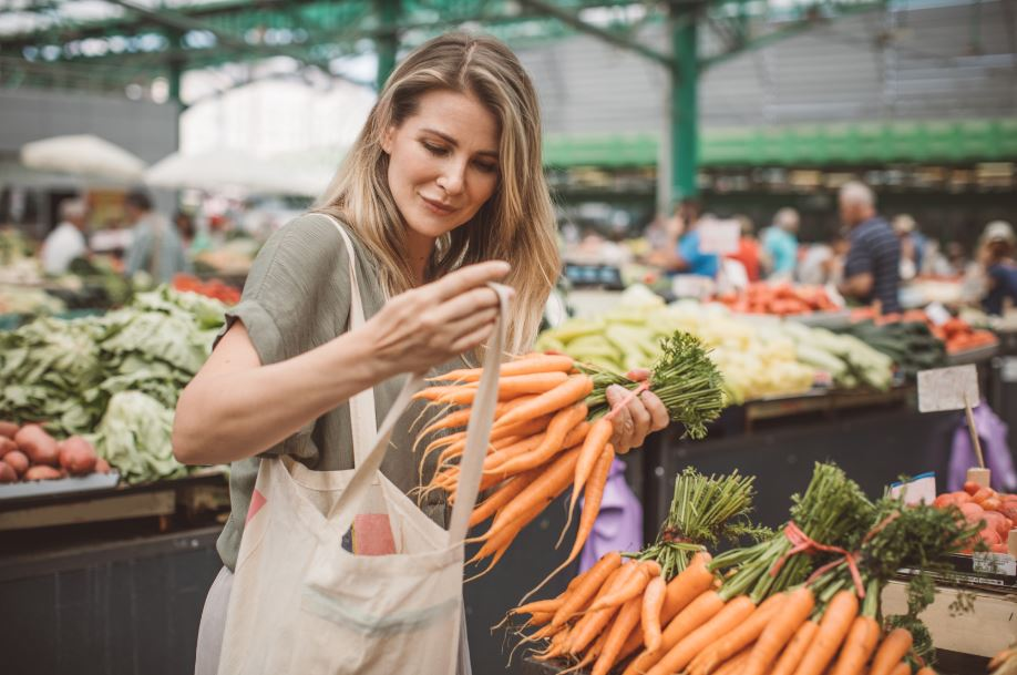 woman shopping at a Los Angeles farmers market with a canvas bag