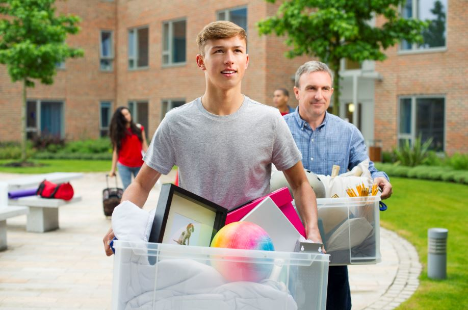 father and son carrying plastic bins toward a college dorm