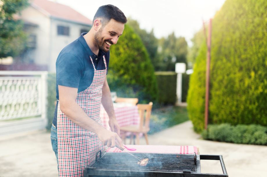 man heating up and cleaning a charcoal grill