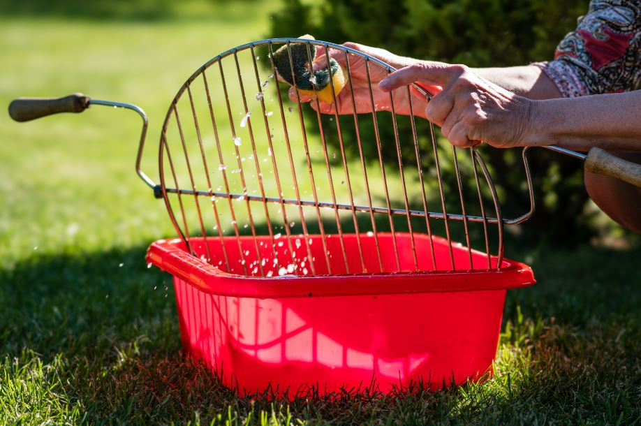 woman scrubbing a charcoal grill grate in soapy water