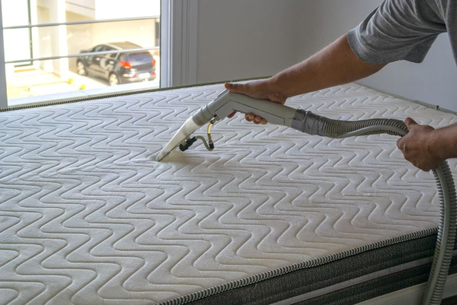 someone following the vacuum steps of how to clean a mattress