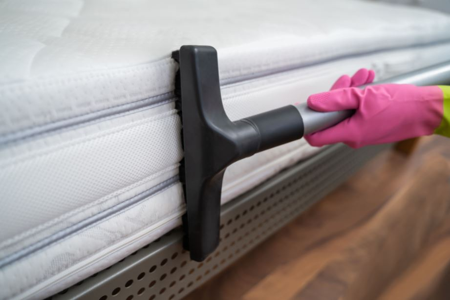 someone wearing gloves and vacuuming the side of a mattress