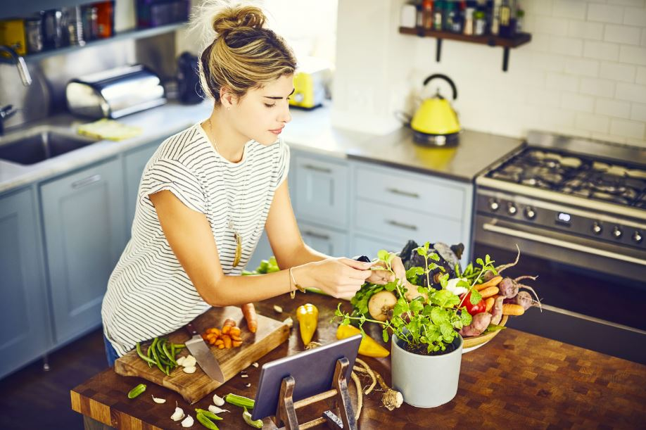 woman clipping mint from her indoor herb garden