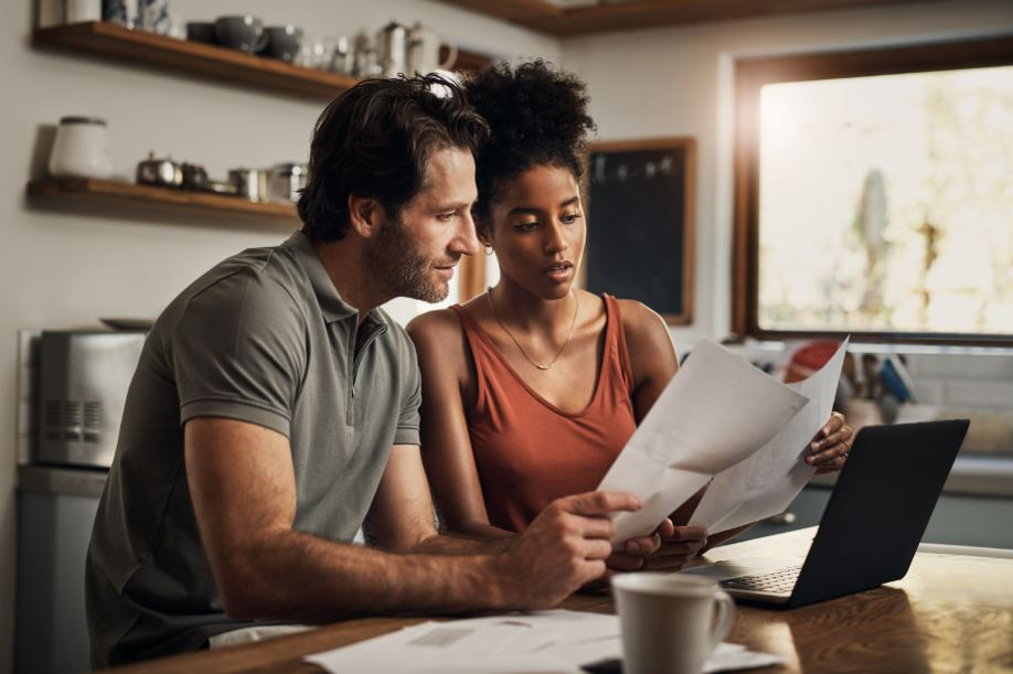 couple looking at financial documents as they start to save for a down payment