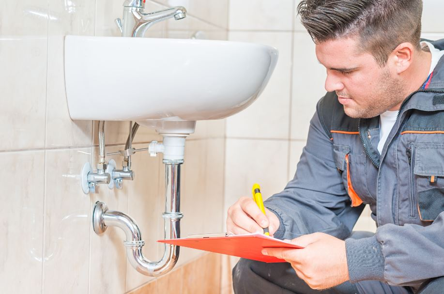 professional inspector checking the plumbing in a house on the market
