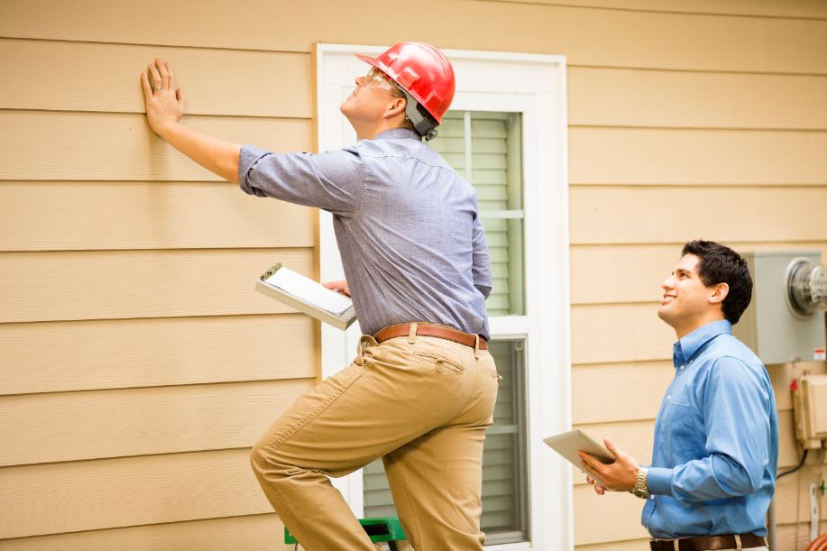potential homebuyer and professional inspector following a home inspection checklist