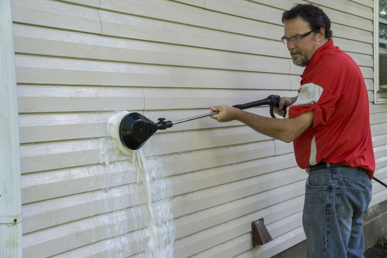man washing mold off of his home's exterior siding