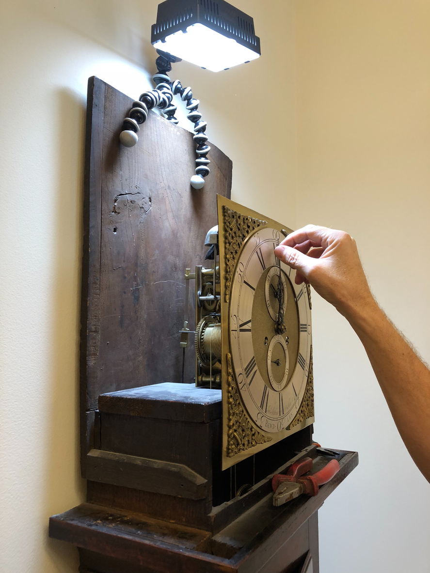 someone disassembling the parts of a grandfather clock