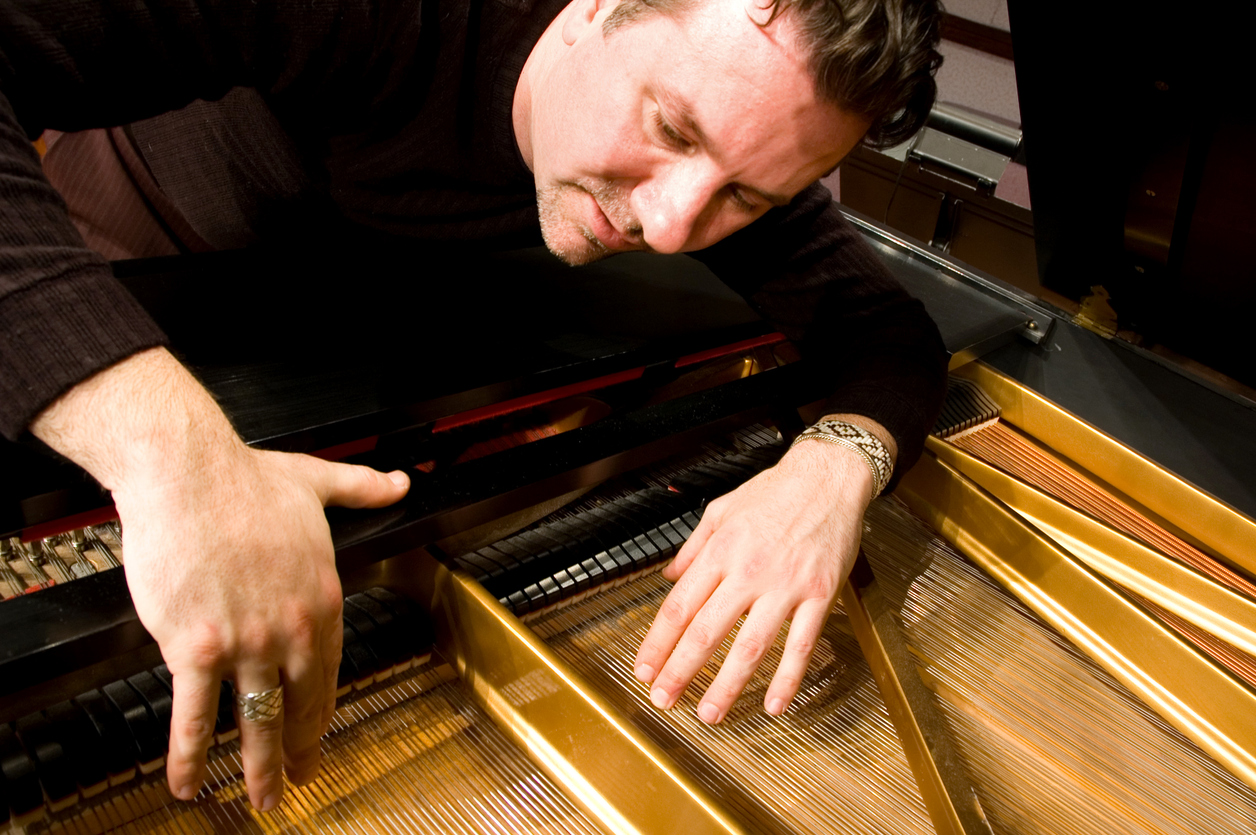 man reassembling and tuning his piano after a move