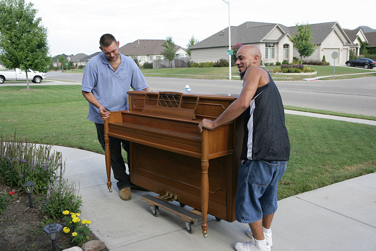 a team of DIY movers moving a piano on a dolly