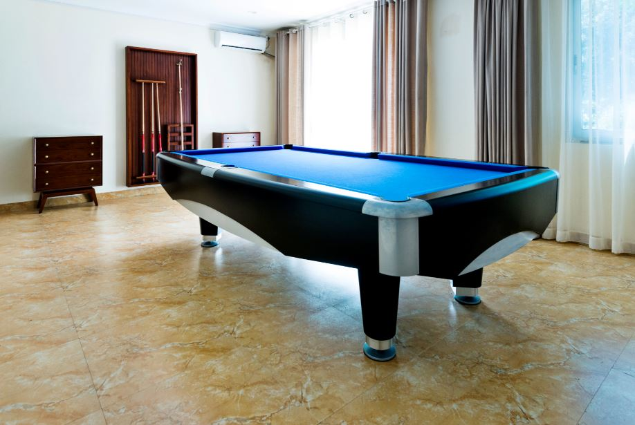 a pool table on furniture sliders in a game room of a new house