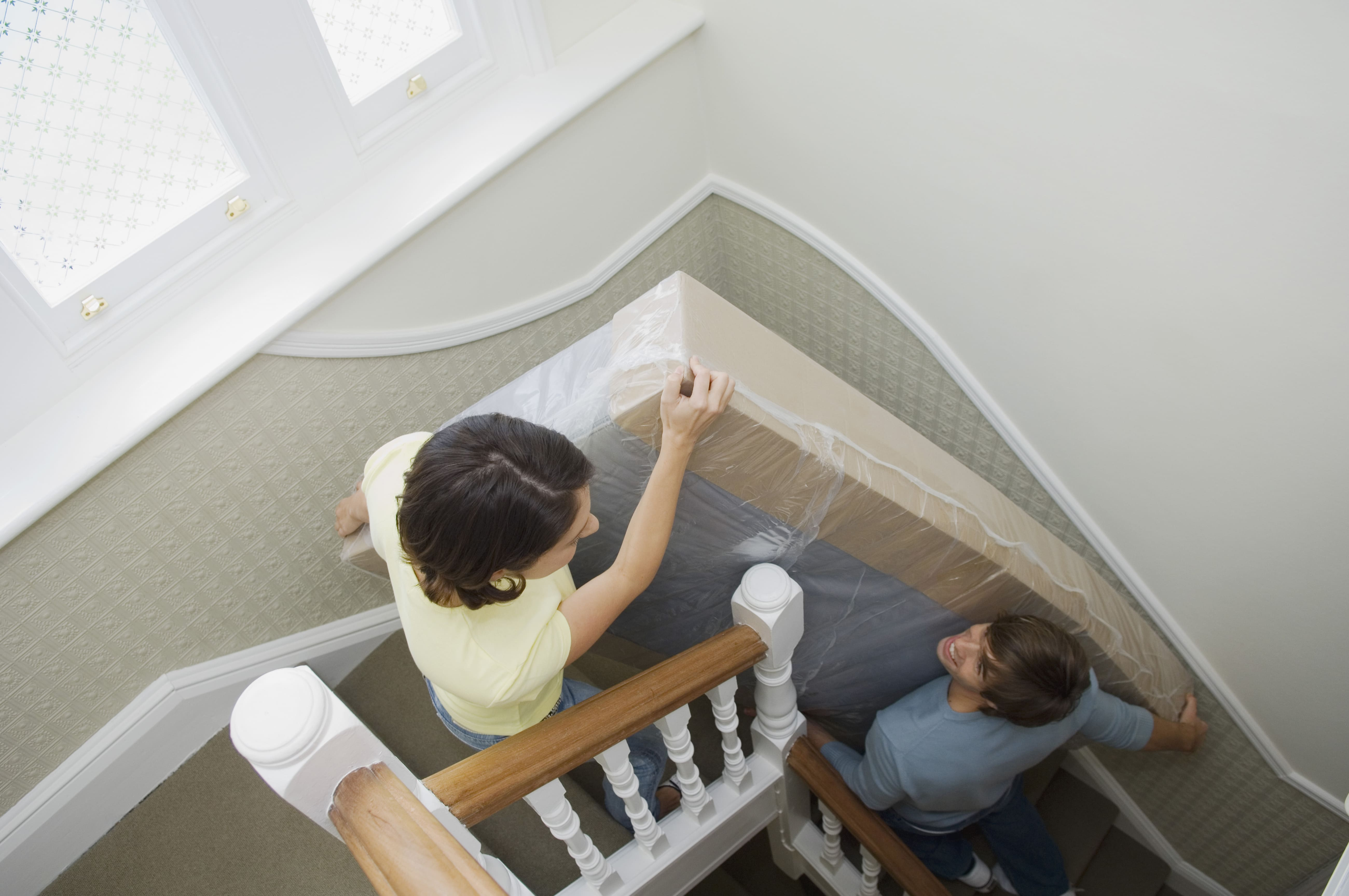 couple moving a mattress packed in a mattress bag down the stairs