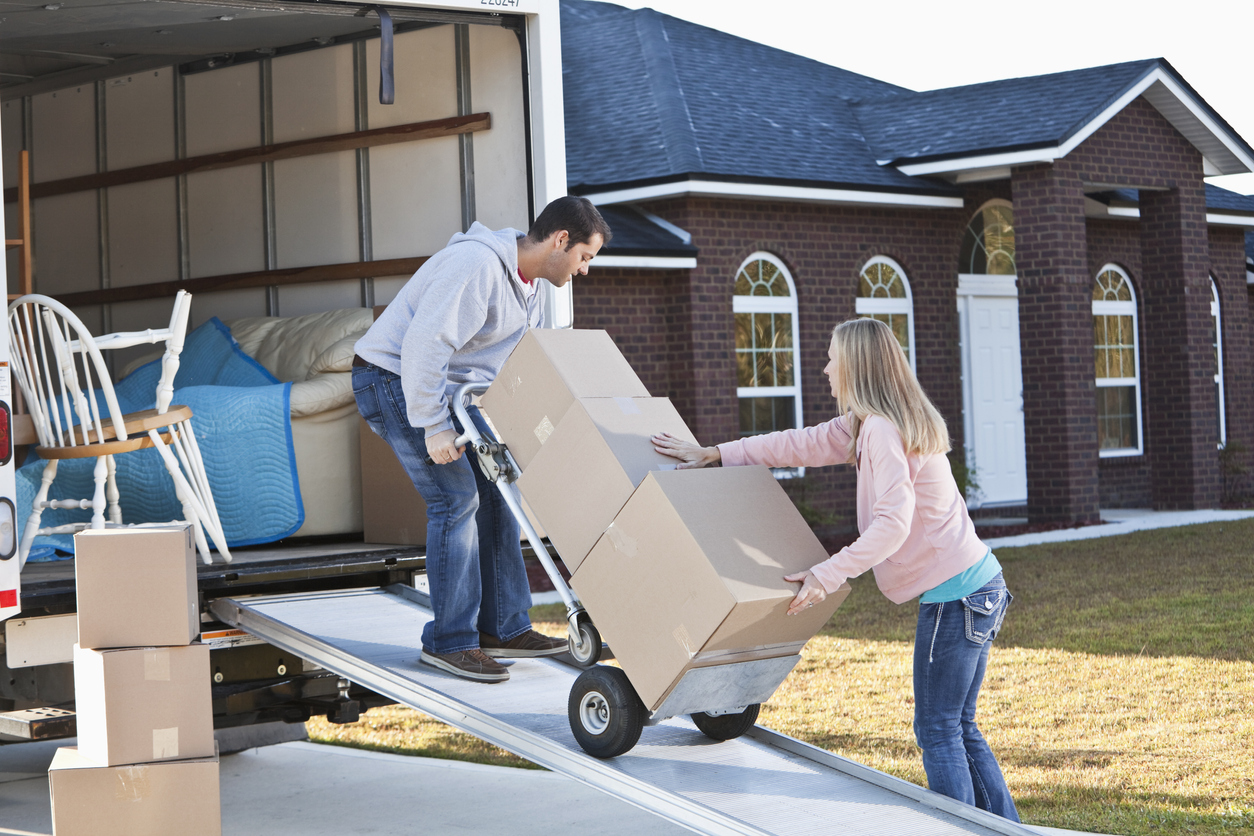 Couple packing up a moving truck on their own
