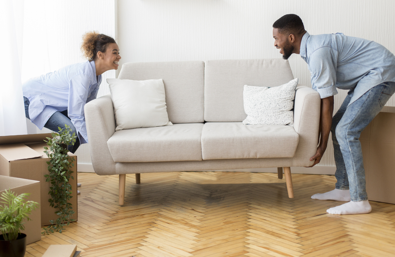 couple moving their couch on wood floors