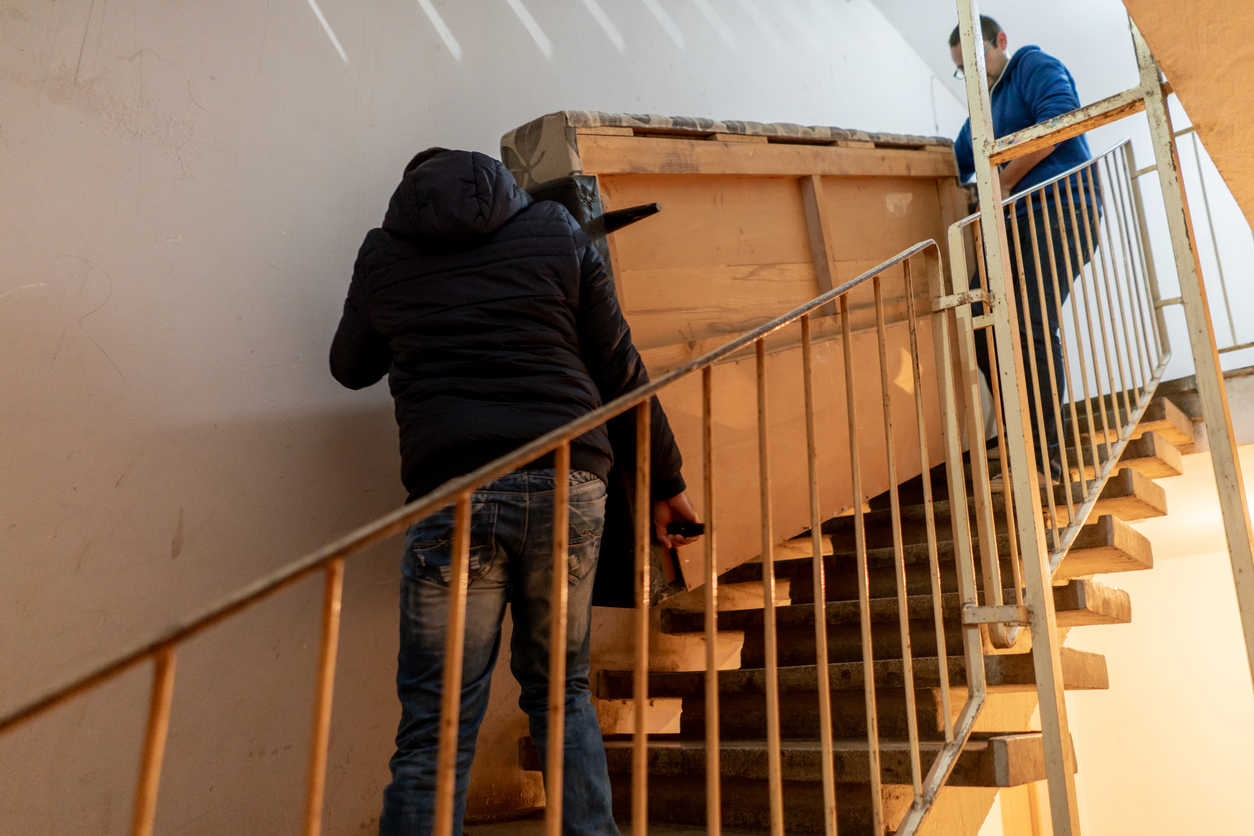 Two young men are carrying a heavy couch downstairs