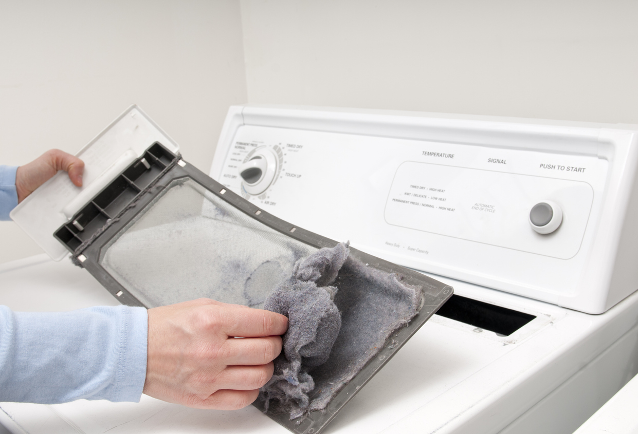 Cleaning out a dryer trap before moving the appliance