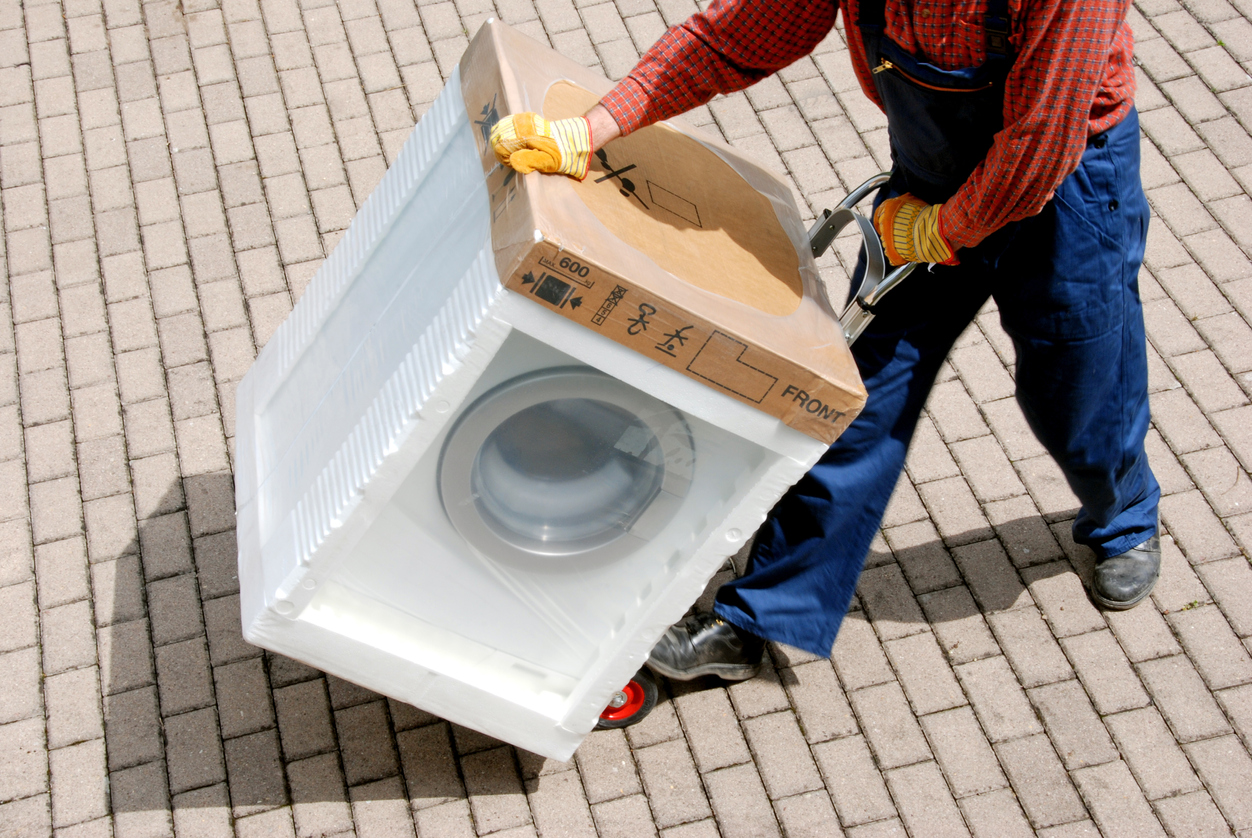 Man moving a washer protected with cardboard and foam on a dolly