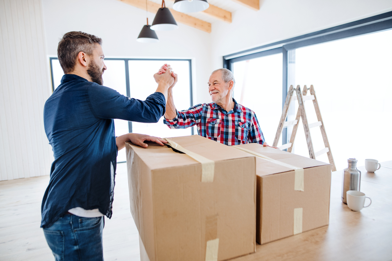 Older man having people help him move boxes