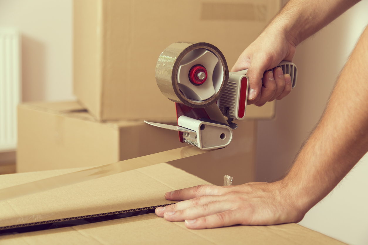 close-up of someone using a tape dispenser to seal a moving box