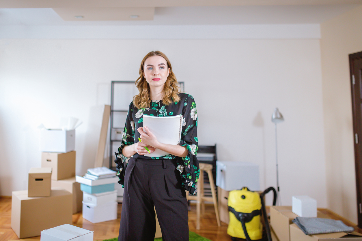 Woman creating a first apartment checklist as she moves in