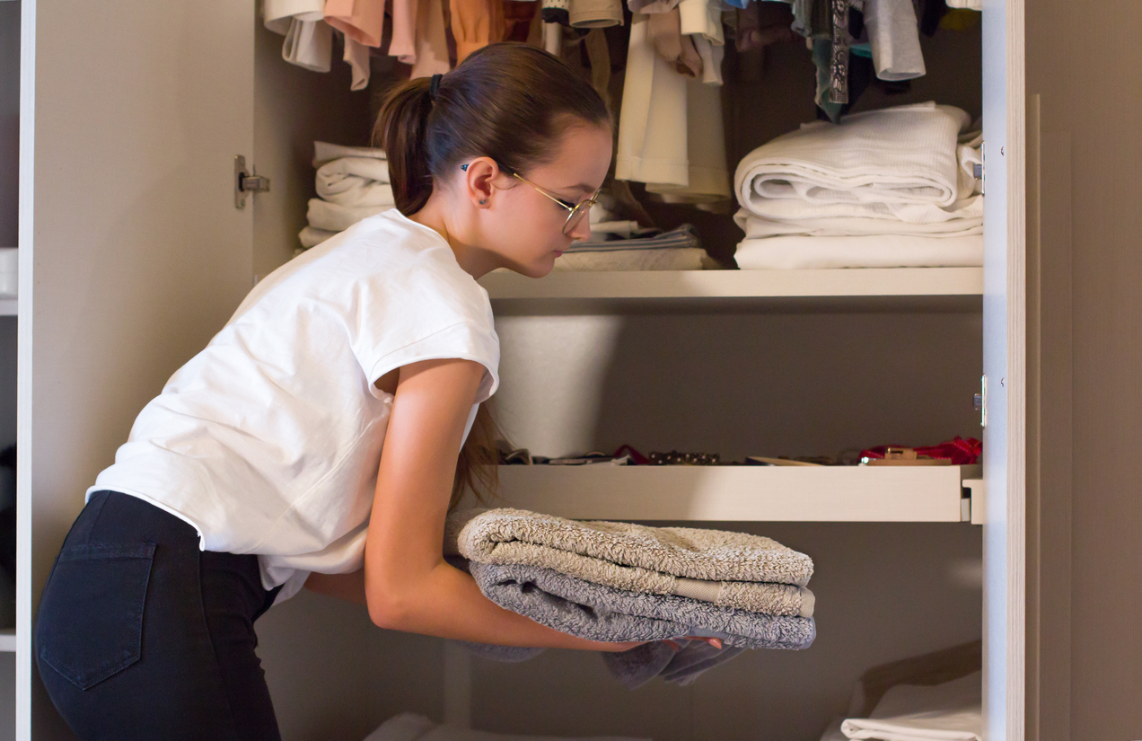 Woman organizing extra blankets in her apartment's linen closet