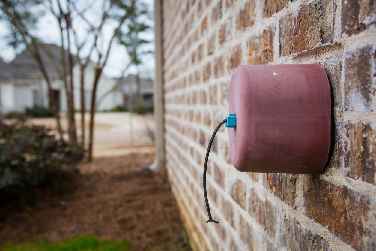 A faucet cover on a spigot along a home's exterior wall