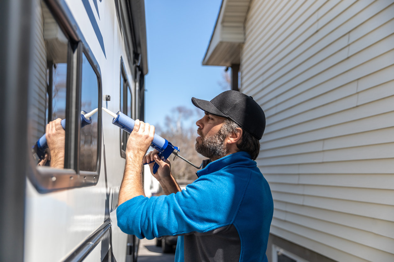 Man applying sealant around his camper windows to winterize it
