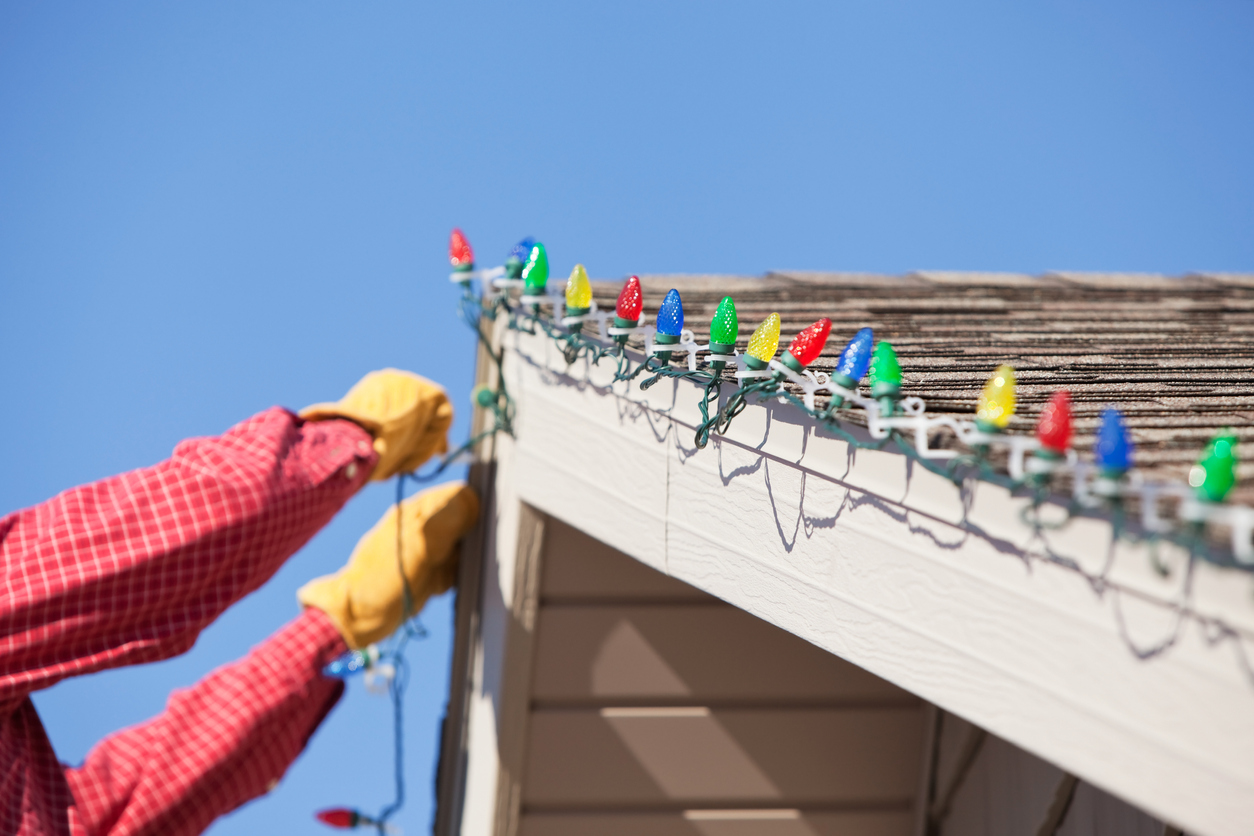 Person hanging Christmas lights along a roof peak