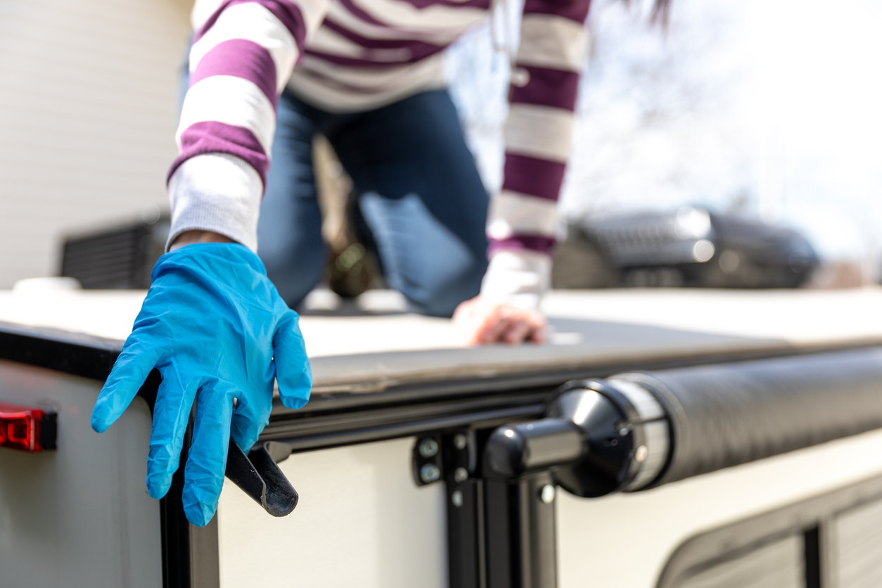 Woman cleaning the awning of her camper trailer