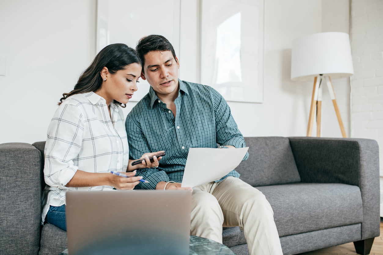 Couple looking at their moving insurance policies before a DIY move