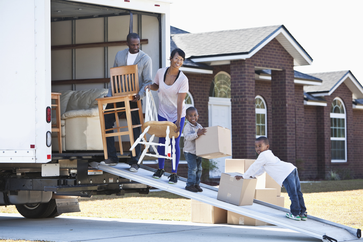 Family loading furniture along the sides of a moving truck