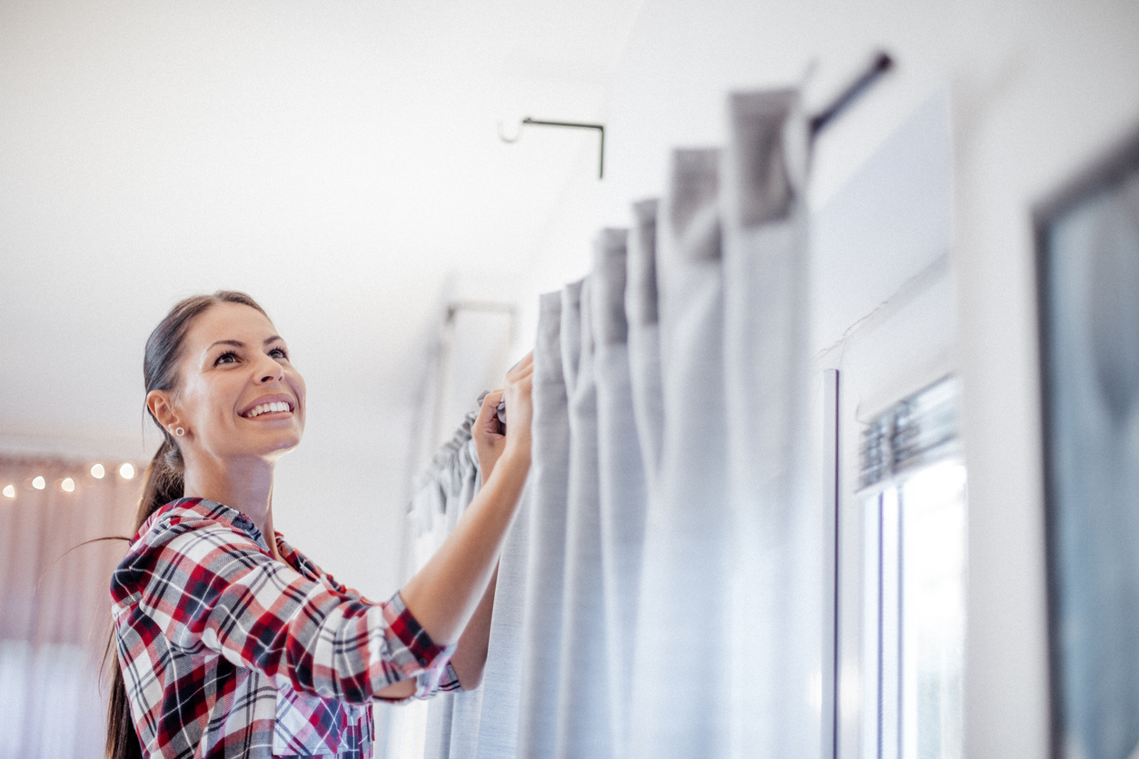 Homeowner hanging curtains in her new home