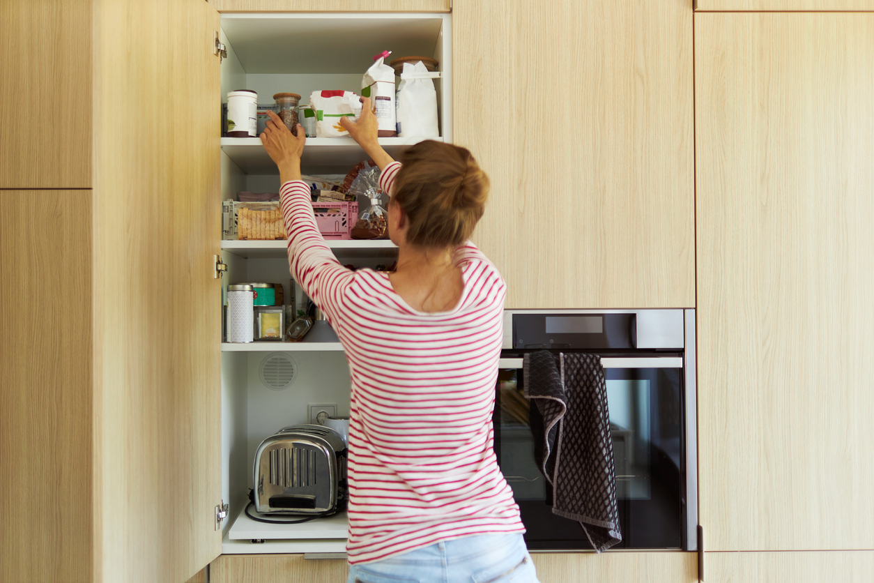 Homeowner organizing home essentials in her kitchen
