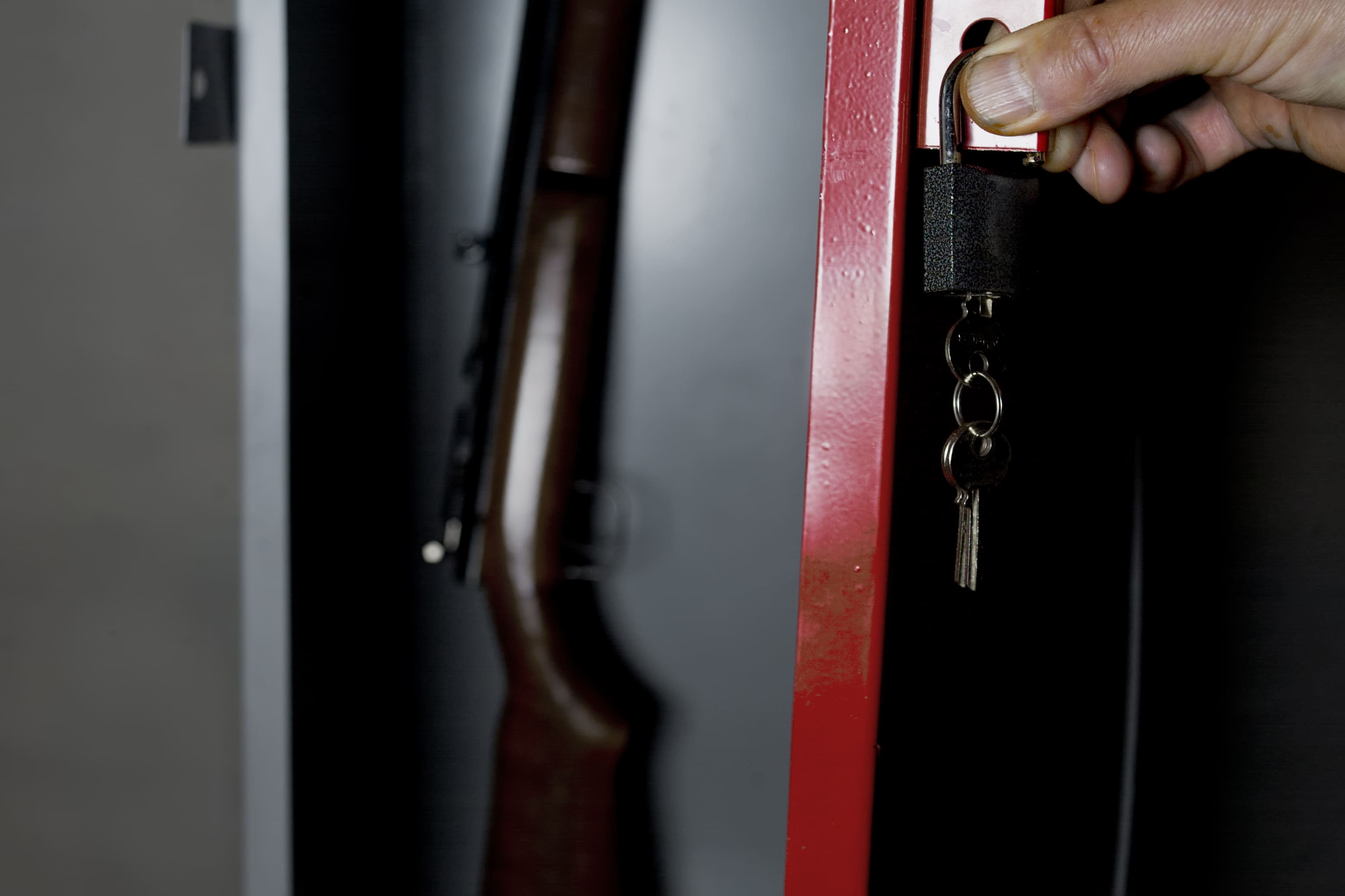 Man opening a home gun safe with a rifle in it