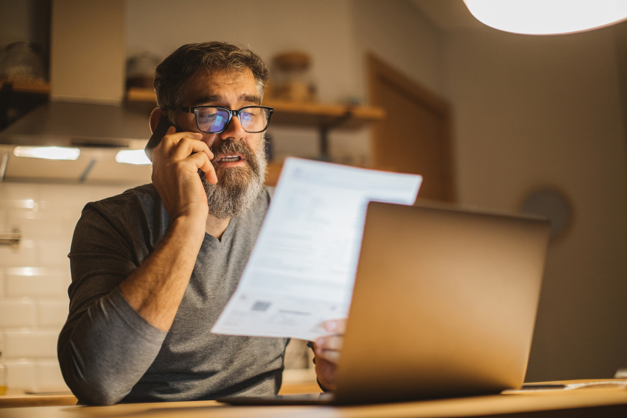 Man reading his lease agreement to see the financial penalties of terminating a lease agreement early