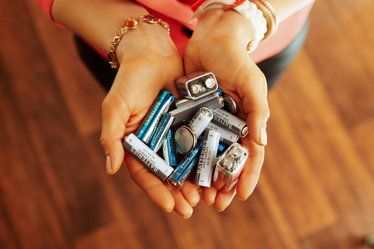 Someone holding a handful of different types of batteries